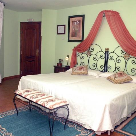 Habitacion Río Miera con dos amplia camas de 105, ilustrado con un dosel caldera, con una señorial terraza para las tardes soleadas